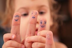 Child holds hand with  drawn persons Royalty Free Stock Image