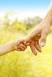 Child holds the hand of parent Stock Photo