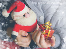 Child holds in his hands gift box and toy Santa Claus Royalty Free Stock Photos
