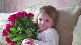 Happy baby holding a big bouquet of scarlet roses.A gift for mother`s birthday. The child holds a large bouquet of scarlet roses stock video
