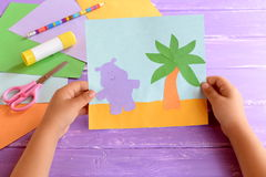 Child holds a paper card with a Hippo and a palm tree. Colored paper sheets, scissors, pencil, glue stick Royalty Free Stock Photo