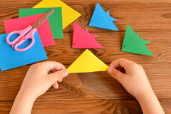 Child holds paper sheet in his hands and making origami fish Royalty Free Stock Photo