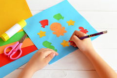 Child holds a pencil and draws. Child doing a card with sea animals and fish Stock Images