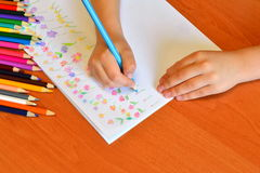 Child holds a pencil in hand and draws a meadow with flowers. A set of pencils. Children's art. Kindergarten drawing lesson Royalty Free Stock Photos