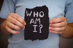 Child holds piece of black paper with question Who am I? Royalty Free Stock Photos