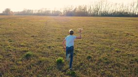 The child runs across the field, holding a plane, simulates flight. Autumn Sunny day. Outdoor entertainment stock video footage