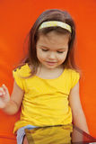 Child holds the plate on an orange background Stock Photo