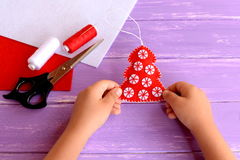 Child holds a red felt Christmas tree ornament in his hands. Red felt fur tree decorated with white balls Stock Images