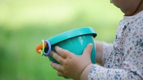 Child holds sand bucket close up on green blurred background, summer day stock video
