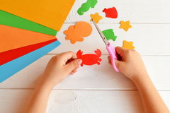 Child holds a scissors and cuts paper crab. Art lesson in kindergarten. Paper sea animals. Kids crafts royalty free stock image