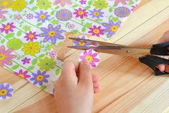 Child holds scissors and paper flower in his hands. Child cuts flowers fragments out paper napkin for decoupage Royalty Free Stock Images