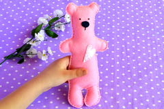 Child holds a small felt Teddy bear in his hands. Pink felt Teddy bear toy. Children toy Stock Images