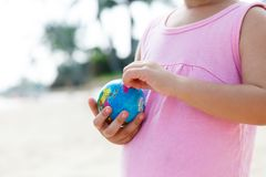 A child holds a small globe in his hands.Closeup. Small child holds a mini globe against a tropical beach background Royalty Free Stock Photo