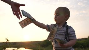 A child holds a stack of money, gives them to adult one by one bill, slow motion. A child holds a stack of money and gives them to adult one by one bill. He is stock footage