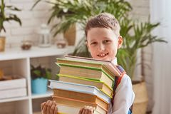 The child holds a stack of textbooks royalty free stock photography
