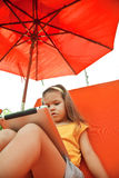 Child holds a tablet on a lounger on the beach under an umbrella Royalty Free Stock Photos