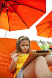Child holds a tablet on a lounger on the beach under an umbrella Royalty Free Stock Images