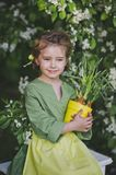 Portrait of a girl against the backdrop of flowering trees 8271. The child holds a tub of sprouted leek stock photography