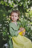 Portrait of a girl against the backdrop of flowering trees 8272. The child holds a tub of sprouted leek Stock Images