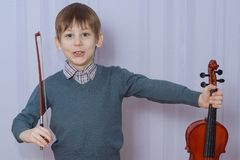 Child holds the violin. Cute young boy holds the children`s violin Stock Photos