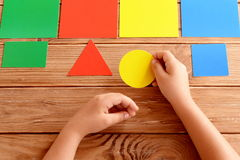 Child holds a yellow cardboard circle in his hands and puts on a corresponding color card. Child learns colors. Set of colored cards for kids of preschool age stock photo