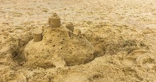 Child holiday built sandcastle with towers on a beach sand landscape royalty free stock images