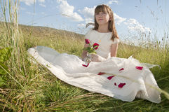 Child in holy communion dress. Young girl in white holy communion dress in countryside field with blue sky and cloudscape background Royalty Free Stock Image