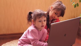 A child at home with a laptop. Family with laptop sister with a laptop at home, sitting on the floor with a laptop, emotional with laptop stock video