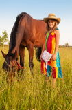 Child with horse. Cute little girl in a cowboy hat with a horse on a green meadow Royalty Free Stock Photography