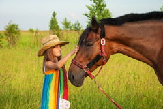 Child and horse. Little girl in cowboy hat talking with horse in meadow Stock Photo