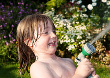 Child hosepipe water summer garden splash. Child playing with hosepipe in garden. boy play water games in summer on lawn Royalty Free Stock Images