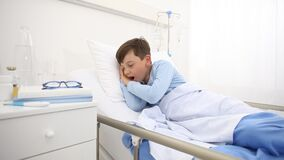 Child in hospital falls asleep yawns before resting his head on the pillow lying alone in bed