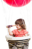 Child on hot air balloon watching through spyglass Stock Photography