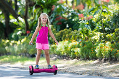 Child on hover board. Kids ride scooter. Child on hover board. Kids riding scooter in summer park. Balance board for children. Electric self balancing scooter royalty free stock images