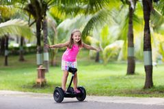 Child on hover board. Kids riding scooter. In summer park. Balance board for children. Electric self balancing scooter on city street. Girl learning to ride stock photos