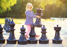 Child with huge chess figures. Outdoor Royalty Free Stock Photos