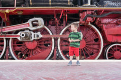 Child and a huge steam engine wheels Stock Photography