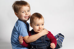 Child hugging baby Stock Images