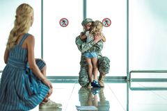 Child hugging father in military uniform Stock Photos