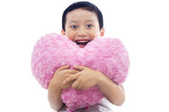 Child hugging a heart pillow Stock Photo