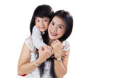 Child hugging her mother in studio Royalty Free Stock Image