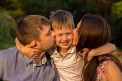 Child hugging his mother and father. Stock Photos