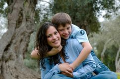 Child hugging his mother smiling on an autumn afternoon royalty free stock image