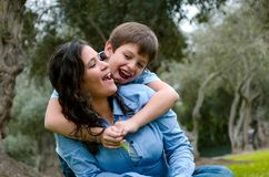 Child hugging his mother smiling on an autumn afternoon royalty free stock photos