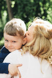 Child hugging mother outdoors Royalty Free Stock Image