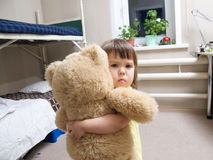 Child hugging teddy bear toy indoor in her room Royalty Free Stock Photo