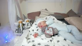 Child hugging a toy while sleeping, cute little boy, Small child sleeps, baby lying on the bed in the sliders and cap stock footage