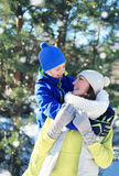 Child hugs his mom and have fun together in winter Stock Photography