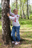Child iby a birch in a forest Stock Photo