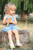 Child with ice-cream. Sitting on stump royalty free stock photo